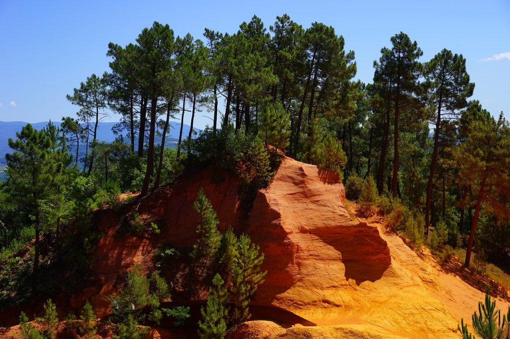 falaise d'ocre avec arbres verts et ciel bleu